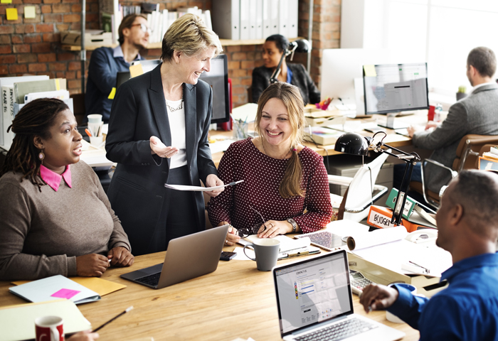 team members smiling while speaking with each other